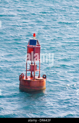 Red buoy with solar panels and red light floating in the Caribbean Sea. - Stock Photo
