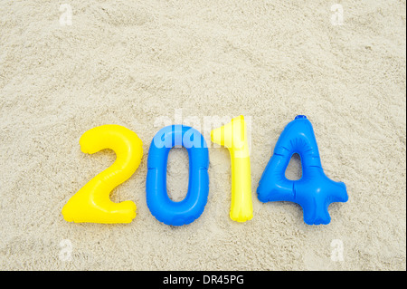 Colorful 2014 message with blue and yellow inflatable numbers on sand beach - Stock Photo