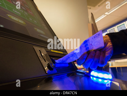 Man putting twenty pound note in fixed odds gaming machine in Corals betting shop. UK - Stock Photo