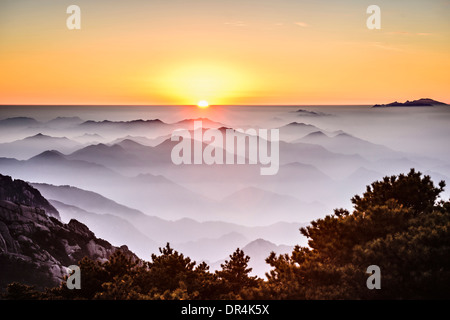 Fog rolling over rocky mountains, Huangshan, Anhui, China - Stock Photo