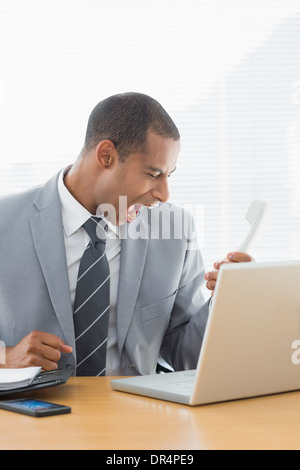 Young businessman shouting into the phone at office - Stock Photo