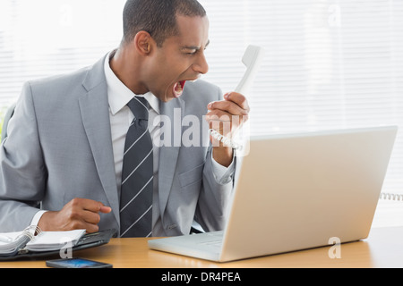 Businessman shouting into the phone at office - Stock Photo