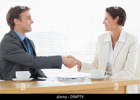 Smartly dressed couple shaking hands in business meeting - Stock Photo