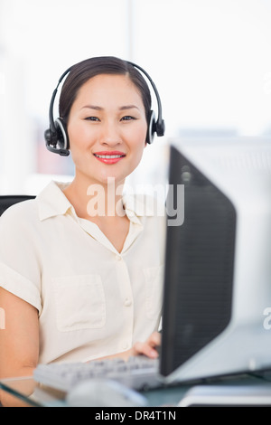 Female executive with headset using computer at desk - Stock Photo