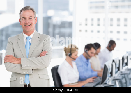 Happy businessman with executives using computers in office - Stock Photo
