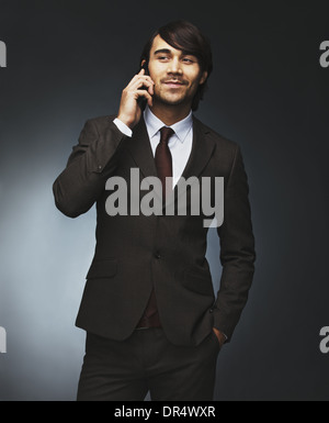 Portrait of handsome young male business executive using cell phone over black background. Happy young male model - Stock Photo