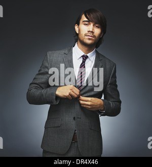 Portrait of handsome young male model buttoning coat. Attractive businessman getting dressed. Mixed race male model - Stock Photo