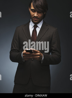 Young asian business man text messaging on his smartphone on black background. Attractive male model in suit holding - Stock Photo
