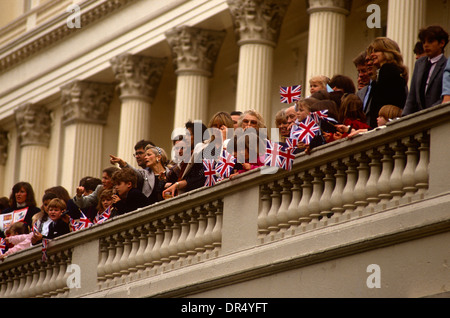Members of English society look down from a balcony during the annual Trooping of the colour parade in the Mall. - Stock Photo
