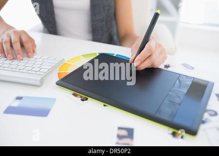 Female photo editor using graphics tablet - Stock Photo
