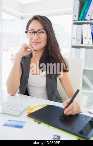 Smiling casual female photo editor using graphics tablet - Stock Photo