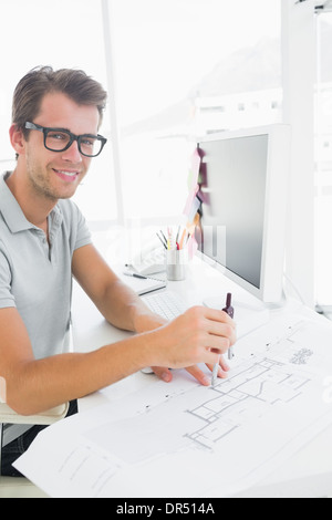 Side view of a smiling young man using compass - Stock Photo