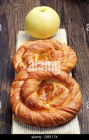 Two round buns with jam and apple on wooden table - Stock Photo