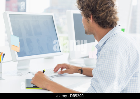 artist drawing something on graphic tablet with pen - Stock Photo