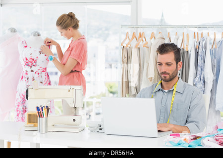 Man using laptop with fashion designer working at studio - Stock Photo