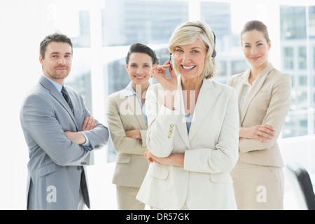 Mature businesswoman wearing headset with colleagues in office - Stock Photo