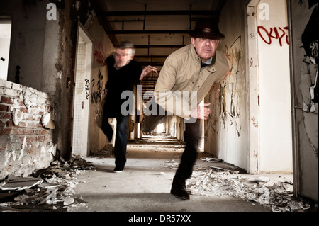 Man runs away from his chaser in an abandoned building - Stock Photo