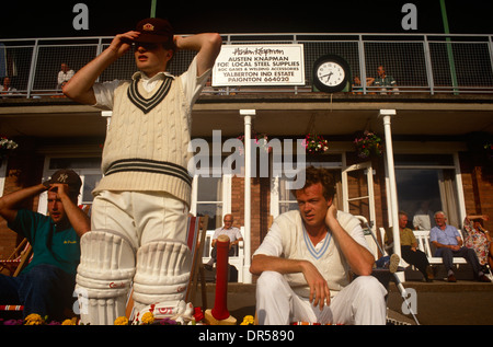 A batsman prepares to walk on to the field during a local club match in Paignton, UK. - Stock Photo