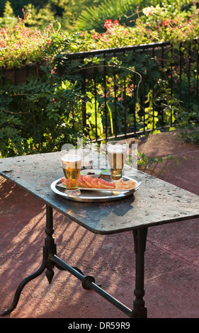 Beer, salami, bread and olives - a light snack at the end of the day on the terrace of a hotel in Italy - Stock Photo