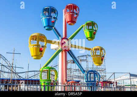 Brightly coloured ferris wheel ride at funfair on Clarence Pier, Portsmouth, Hampshire, UK - Stock Photo