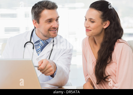 Male doctor showing something on laptop to patient - Stock Photo