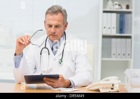Focused doctor sitting at his desk with clipboard - Stock Photo
