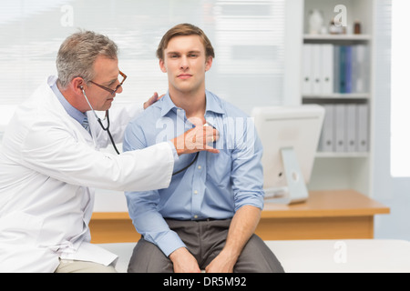 Mature doctor listening to his patients chest with stethoscope - Stock Photo