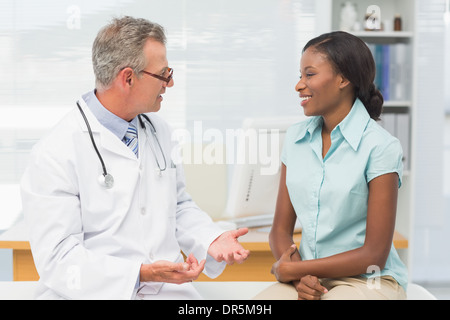Doctor speaking with cheerful young patient - Stock Photo
