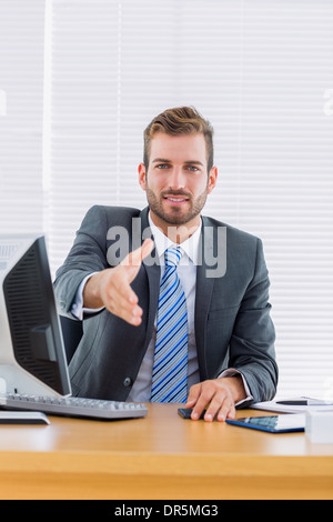 Businessman offering a handshake at office desk - Stock Photo