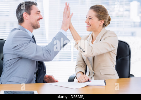 Smartly dressed colleagues giving high five in business meeting - Stock Photo