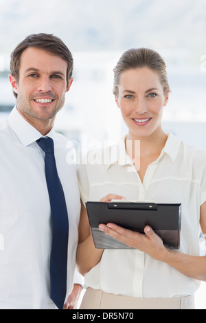 Smartly dressed colleagues using digital tablet - Stock Photo
