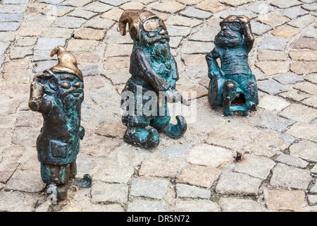 Three of Wroclaw's famous little bronze gnomes, dwarfs or krasnale statuettes. - Stock Photo