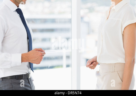 Mid section of executives exchanging business card - Stock Photo