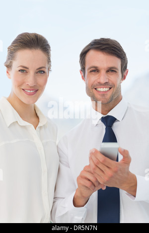 Smartly dressed colleagues with a mobile phone - Stock Photo