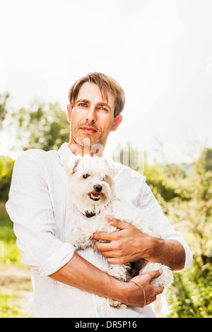 Man with dog in his arms outdoors, Bavaria, Germany - Stock Photo