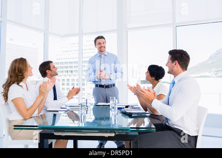 Executives clapping around conference table - Stock Photo