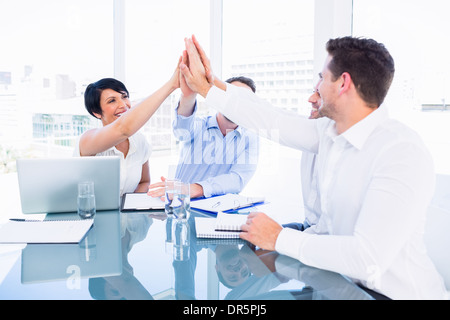 Executives giving high five in a business meeting - Stock Photo