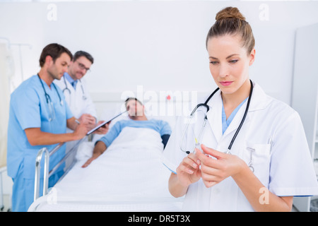 Doctor holding syringe with colleagues and patient at hospital - Stock Photo