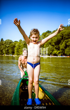 Boy in bathing trunks in a canoe, arms raised, Bavaria, Germany - Stock Photo