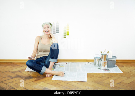 Woman sits on parquet floor, color samples on the wall, Munich, Bavaria, Germany - Stock Photo