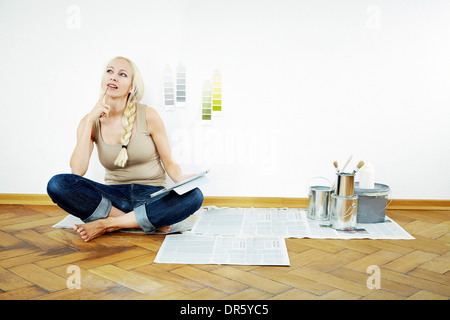 Young woman sits on parquet floor, color samples on the wall, Munich, Bavaria, Germany - Stock Photo