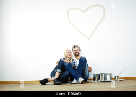 Couple sits on parquet floor, heart shape on the wall, Munich, Bavaria, Germany - Stock Photo