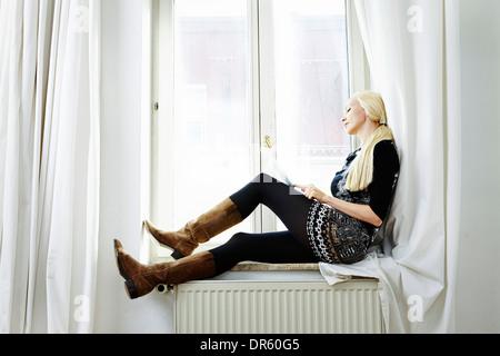 Blond woman sits at window, using computer, Munich, Bavaria, Germany - Stock Photo