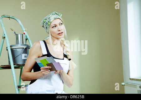 Young woman holding color samples, Munich, Bavaria, Germany - Stock Photo