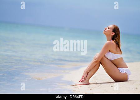 Young woman in bikini relaxes on beach, Lankayan Island, Borneo, Malaysia - Stock Photo