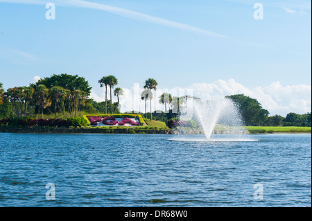 USA Florida PGA National Golf Course Palm Beach Gardens lake water feature fountain blue sky trees lawn flowers - Stock Photo