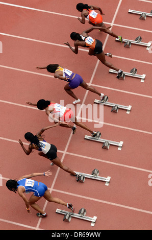 Out of the Starting Blocks in the Women's 100 Yard Dash Heat at the Penn Relays Carnival in Philadelphia, Pennsylvania. - Stock Photo
