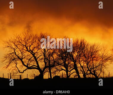 Peak District, Derbyshire, UK.  20th Jan 2014.  At the end of a bright day, a fiery sun illuminates the sky burnt - Stock Photo