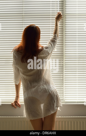 A woman near the window at home - Stock Photo