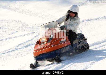 A woman in her early 30s enjoying a snowmobile ride after a fresh snowfall in Quebec, Canada. - Stock Photo